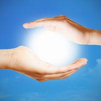 Hände halten Sonne als Meditation Konzept