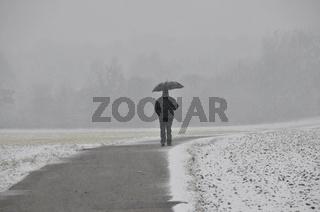 Einsamer Mann mit Regenschirm, Schneefall, Schwäbische Alb, Baden-Württemberg, Deutschland, Europa