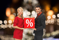 couple with discount sign over christmas lights