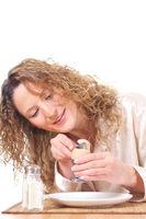 Hübsche Frau köpft Frühstücksei