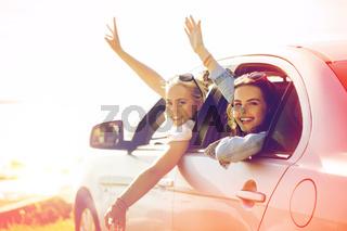 happy teenage girls or women in car at seaside