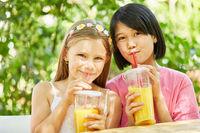 Zwei Mädchen trinken gesunden Orangensaft