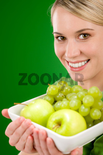 Healthy lifestyle - woman holding bowl with green fruit