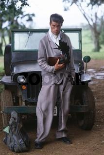 Mann vor Jeep mit Hahn