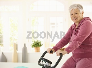 Healthy elderly woman on exercise bike