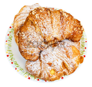 top view of three fresh croissants on plate