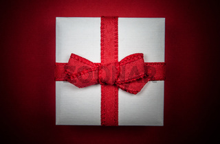 Little white gift isolated on red background
