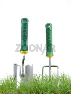 Green grass with garden tools siolated against a white background