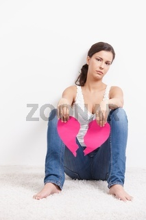 Heart-broken female sitting on floor sadly