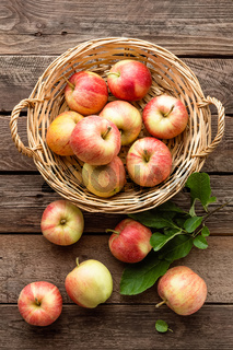 Fresh red apples in wicker basket on wooden table.