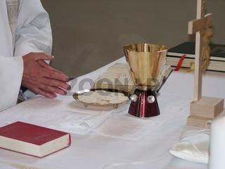 Altar mit Hostien und Wein, betende Hände