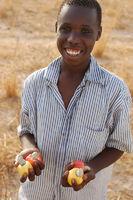 Cashewapfel anbietender Junge aus dem Senegal
