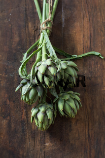 Supplies and materials for artichoke bouquet on wooden background