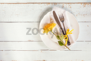 White empty plate, yellow chrysanthemum flowers, napkin, fork and knife tied with a yellow ribbon on light wooden background.
