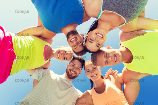 group of happy sporty friends in circle outdoors