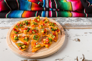 Nachos chips with vegetables on a chopping board and a poncho