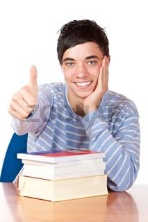 Fröhlicher Schüler sitzt am Tisch mit Büchern und zeigt Daumen