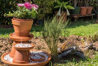 Springbrunnen mit Blume und Kieselsteinen im Garten