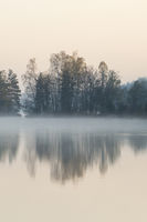at daybreak... calm lake in Sweden in moody light with a little bit of morning mist over the water