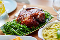roast chicken with garnish of green peas on table