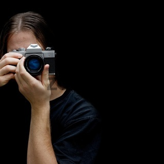 Photographer with an old film camera isolated on black