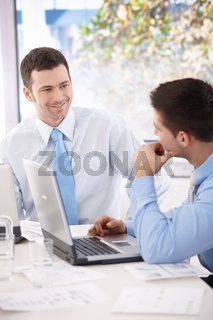 Young businessmen talking at meeting table