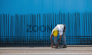 Construction worker installing binding wires to steel bars
