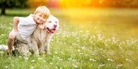 Junge geht mit Golden Retriever Hund Gassi im Park