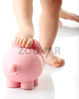 Baby legs on piggy bank