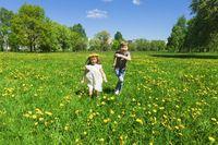 Happy children run on meadow