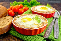 Tartlet meat with egg in pan on board
