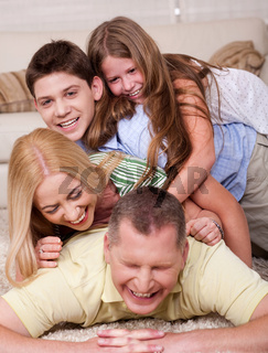 Full portrait of a happy family lying on bed and having great time