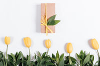 Several yellow tulips and gift box with a bow on a white background