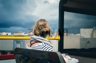 A female tourist is sight seeing on the top deck of a tourist bus.