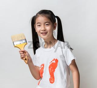 Cute asian girl holding paint brush