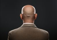 The back of a bald man in suit