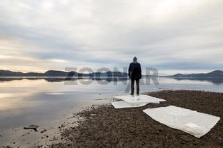 Man standing at the beach, ice floes on dark sand, calm sea, mist and fog. Hamresanden, Kristiansand, Norway