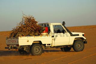 Mit Feuerholz beladener Kleintransporter in der Sahara