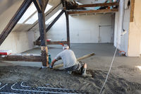Laborer leveling sand and cement screed over floor heating.