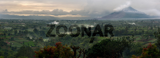 Mount Sinabung Active Volcano with lush green landscape view and cloud filled valley leading to it.
