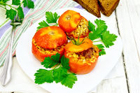 Tomatoes stuffed with bulgur and parsley in plate on table