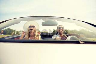 happy man and woman driving in cabriolet car