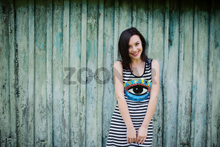 Smiling brunette model girl at dress with stripes background cian wooden background.