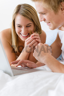 Young couple relax in bed with laptop