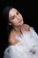 Brunette wearing luxurious white fur coat portrait