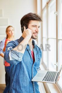 Gründer mit Laptop beim Telefonieren
