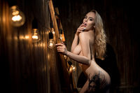 Nude blonde with long locks posing provocative