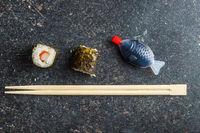 Japanese sushi rolls, chopsticks and fish sauce.