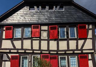 Fachwerkhaus mit roten Fensterlaeden