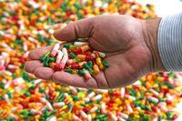 Hand full of medication pill capsules